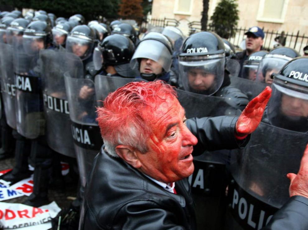 Un manifestante herido junto a la policía.