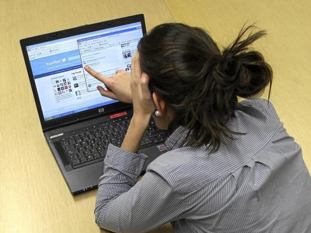 Una joven mira las páginas web de dos de las redes sociales más populares