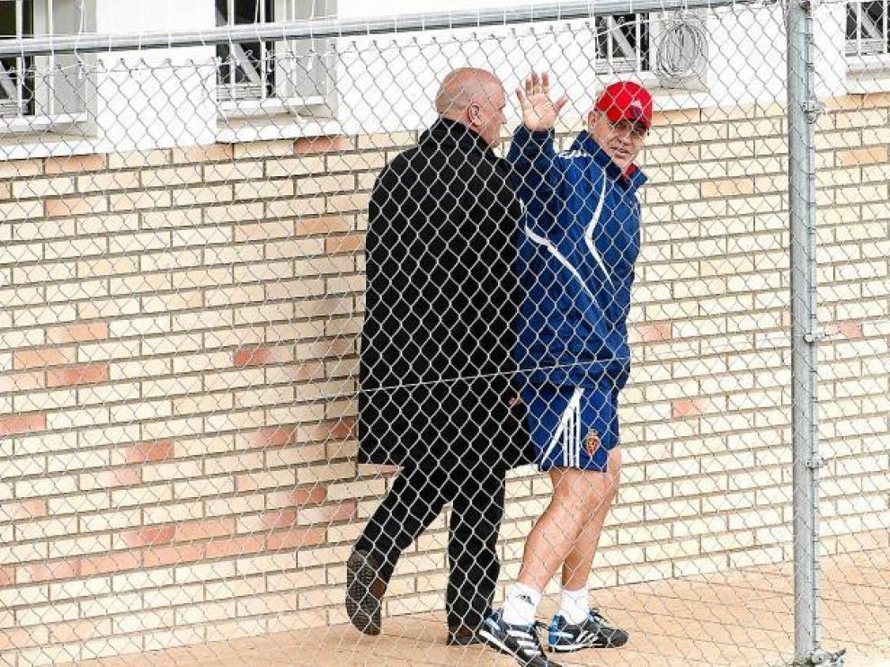 Javier Aguirre, el viernes, saluda acompañado de Pedro Herrera mientras camina por el pasillo de los vestuarios de la Ciudad Deportiva.