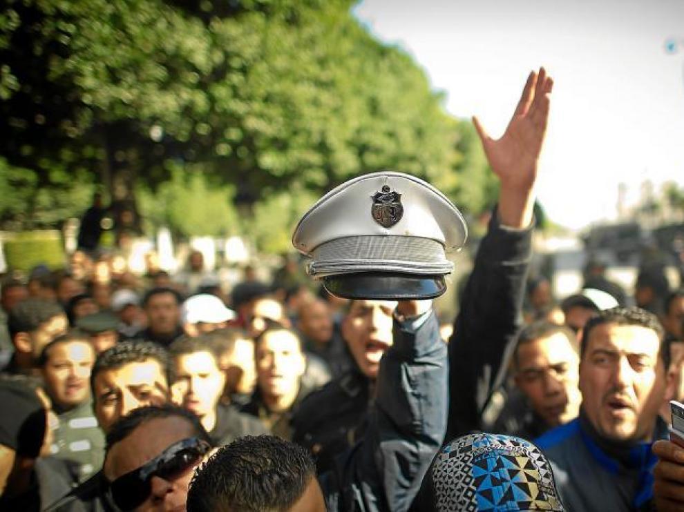 Un manifestante muestra un gorro de la Policía tunecina que ayer se unieron a las protestas.