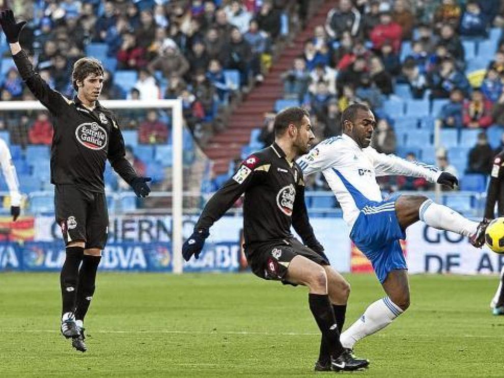 Sinama Pongolle toca la pelota ante la defensa de Lopo.