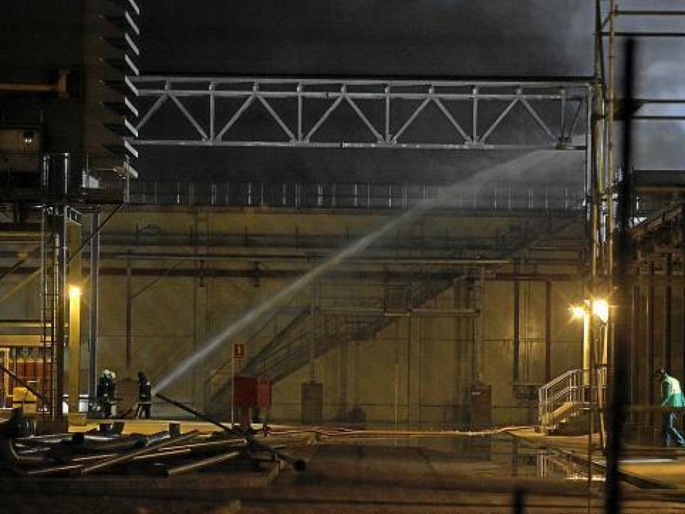 Los bomberos refrescaban anoche los rescoldos del fuego en un almacén de la factoría de Saica.