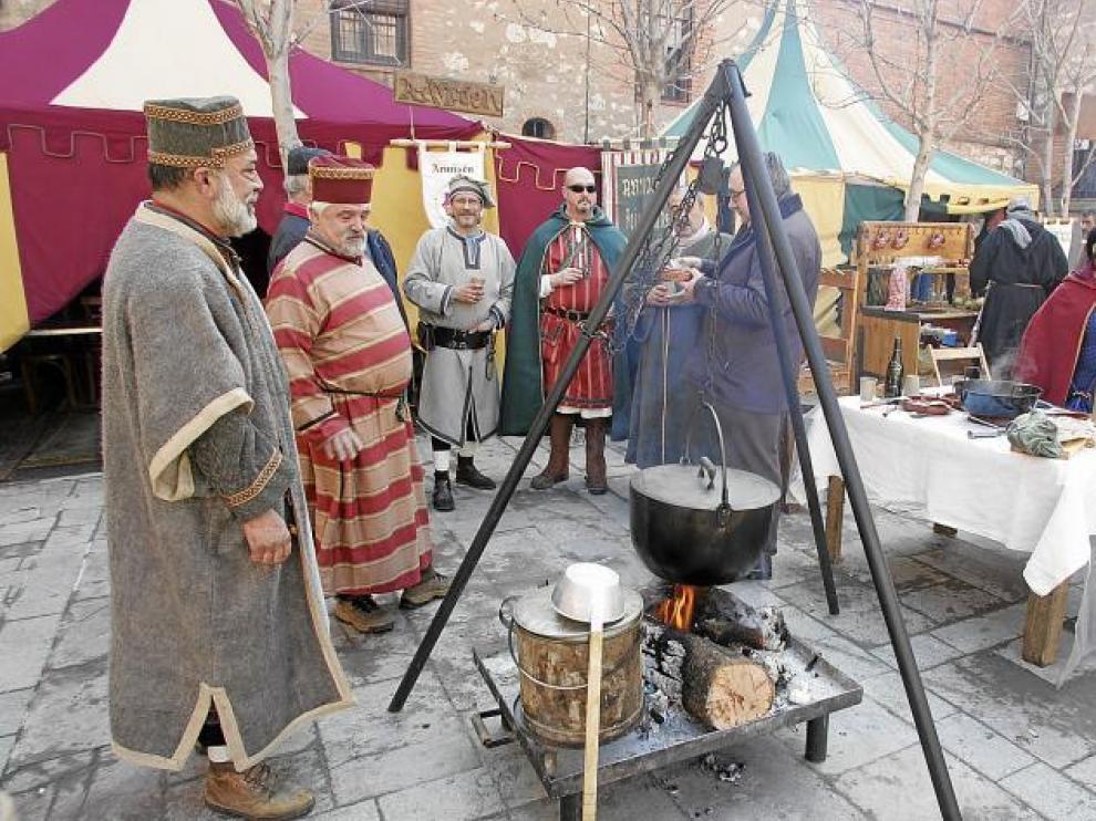 Miembros de uno de los grupos cocinando en la calle, con las jaimas al fondo, en la pasada edición de las Bodas de Isabel.