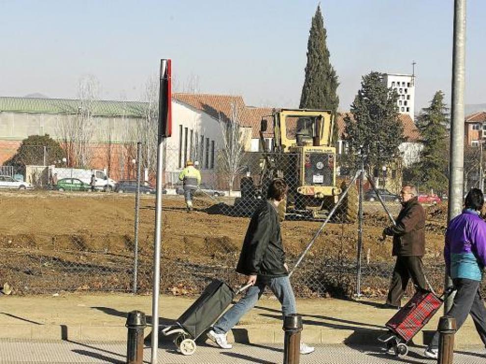 Varios peatones observan las obras en el solar de la cárcel desde la calle Aragón.