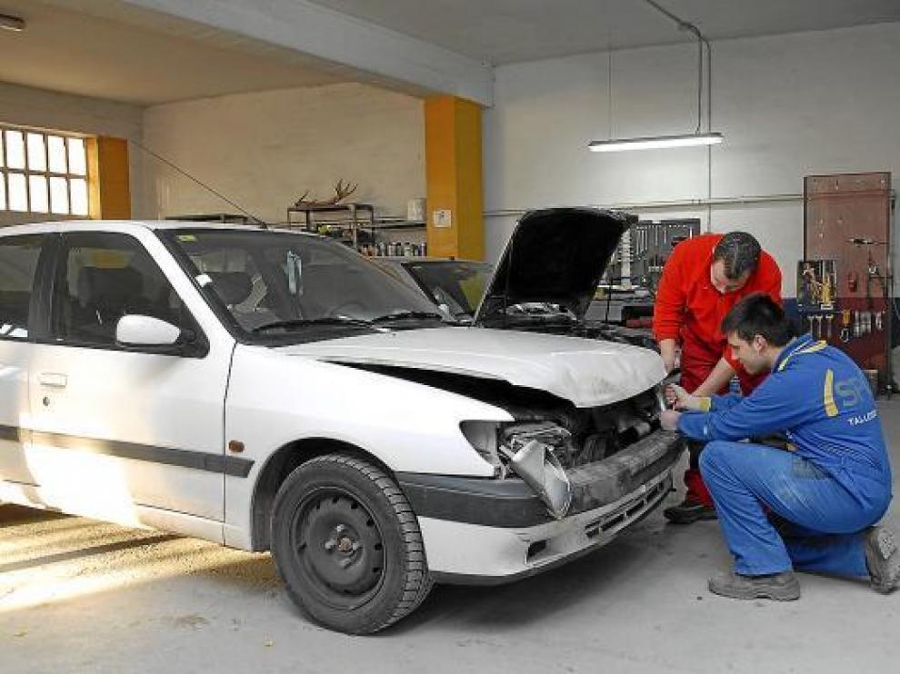 Dos mecánicos de Teruel reparaban ayer los daños de un coche que chocó con un jabalí.