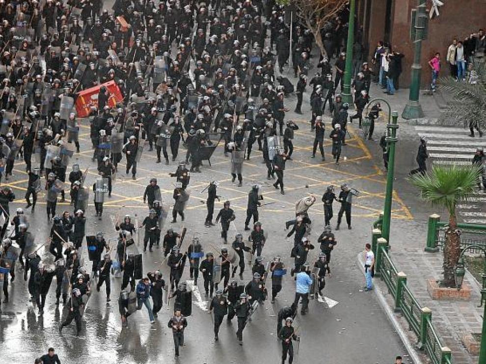 Policías antidisturbios se enfrentan a decenas de personas, ayer en el centro de El Cairo.