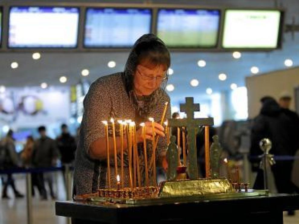 Una mujer enciende una vela, en el aeropuerto de Domodedovo.