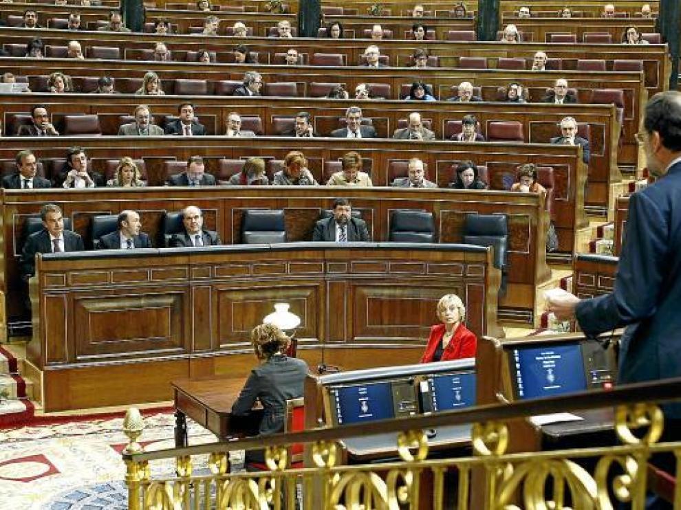 Rajoy (derecha, de espaldas) se dirige al presidente del Gobierno (izquierda), ayer en el Congreso.