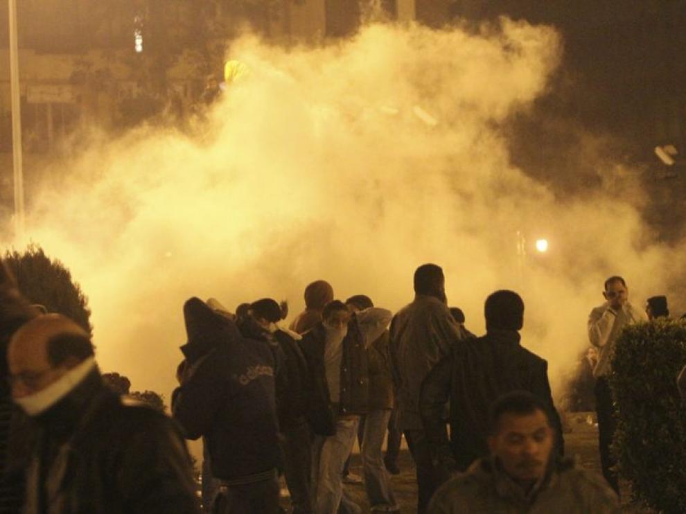 Una nube de gas lacrimógeno cubre a un grupo de manifestantes en El Cairo