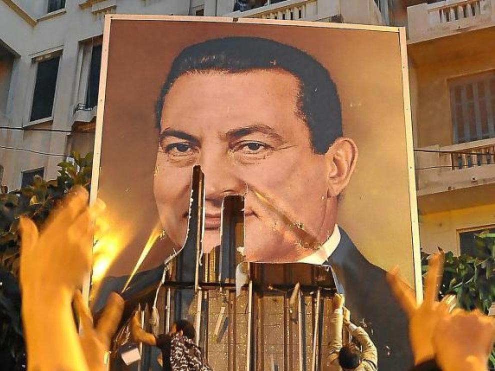 Dos egipcios rompen un cartel con la imagen de Mubarak, ayer en la ciudad de Alejandría.