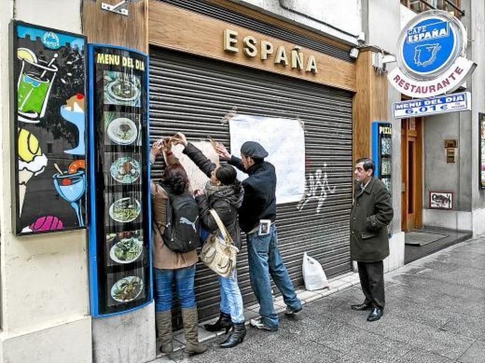 Algunos empleados colocaban ayer carteles reivindicativos en la puerta del bar España.
