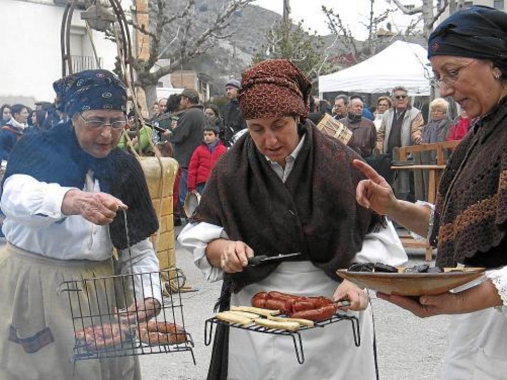 Un grupo de mujeres de la Festa del Tosino de Albelda muestran algunos de los productos del cerdo.