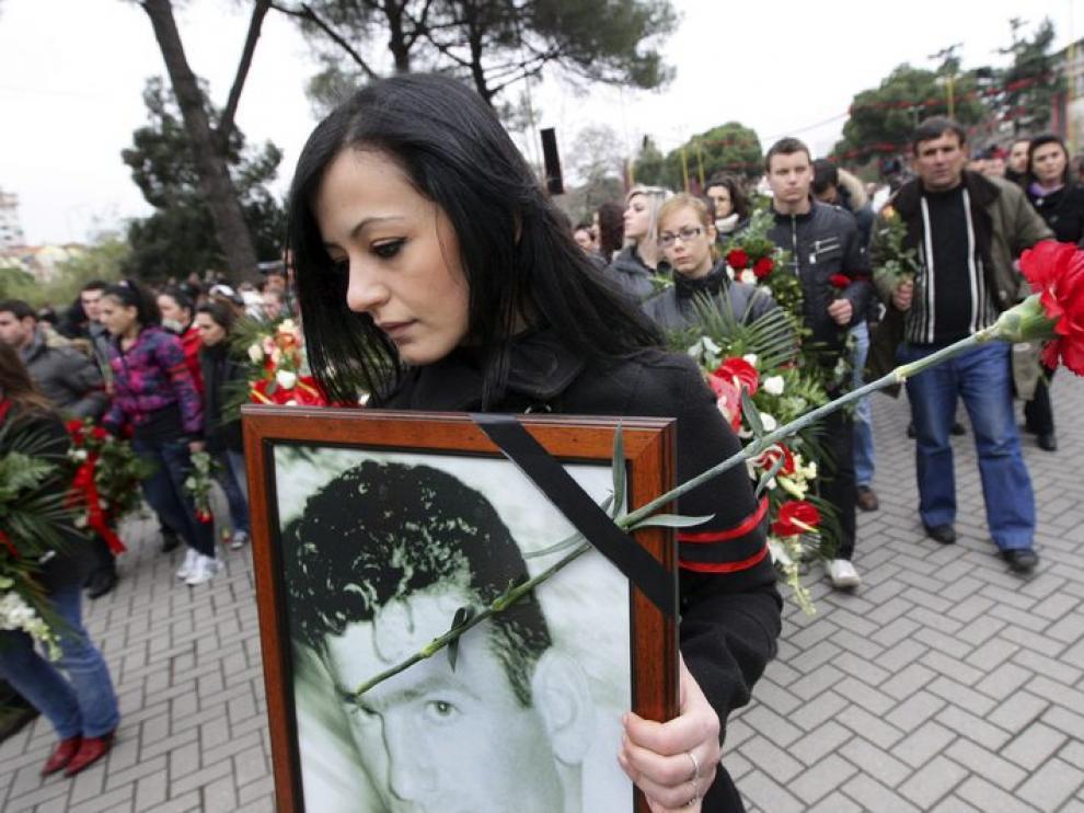 Una manifestante porta un retrato de un fallecido y un clavel