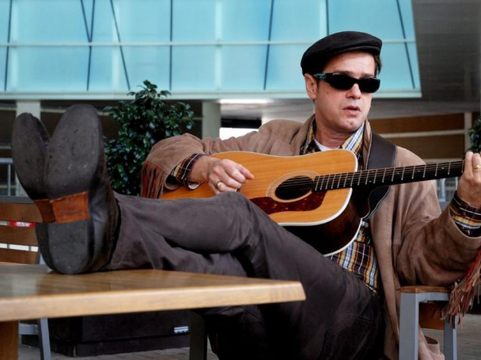 Juan Perro afina su guitarra.
