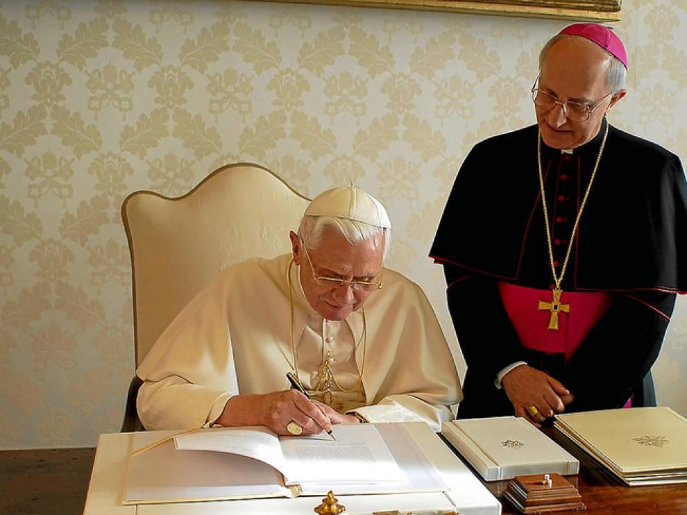 Benedicto XVI escribe en presencia del obispo Fernando Filioni