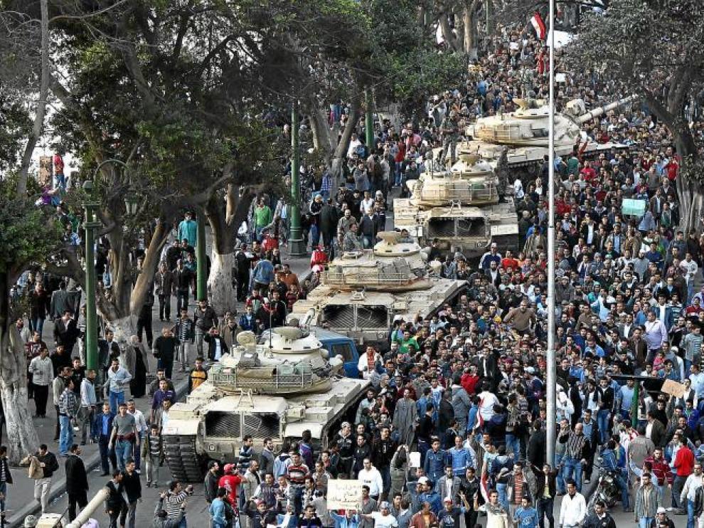 Varios tanques circulan por una calle de El Cairo rodeados por miles de egipcios.