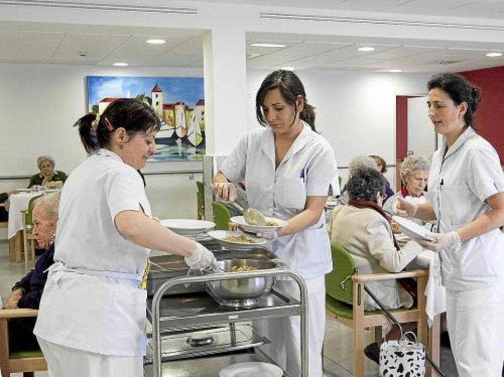 Las auxiliares de la residencia Cai-Ozanam-Oliver, se encargan de servir las comidas.