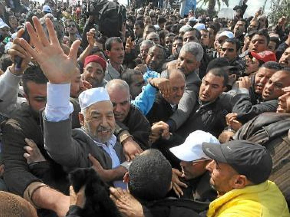 Gannuchi, con gorro blanco, rodeado de seguidores en Túnez.