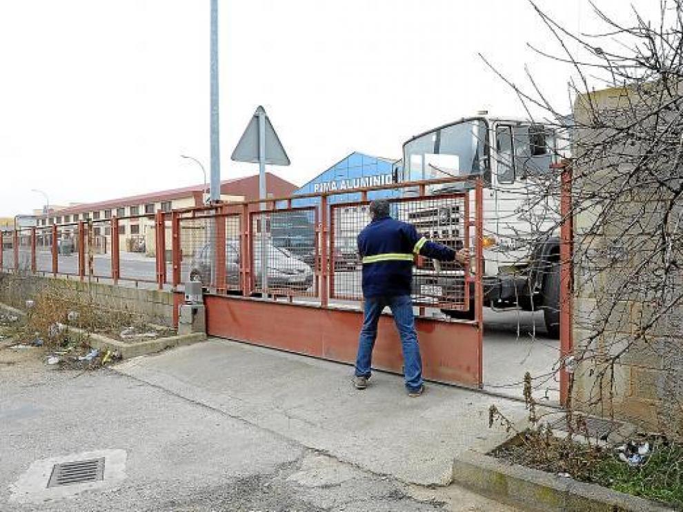 Un operario abre la puerta de la nave municipal a mano por falta de suministro eléctrico.
