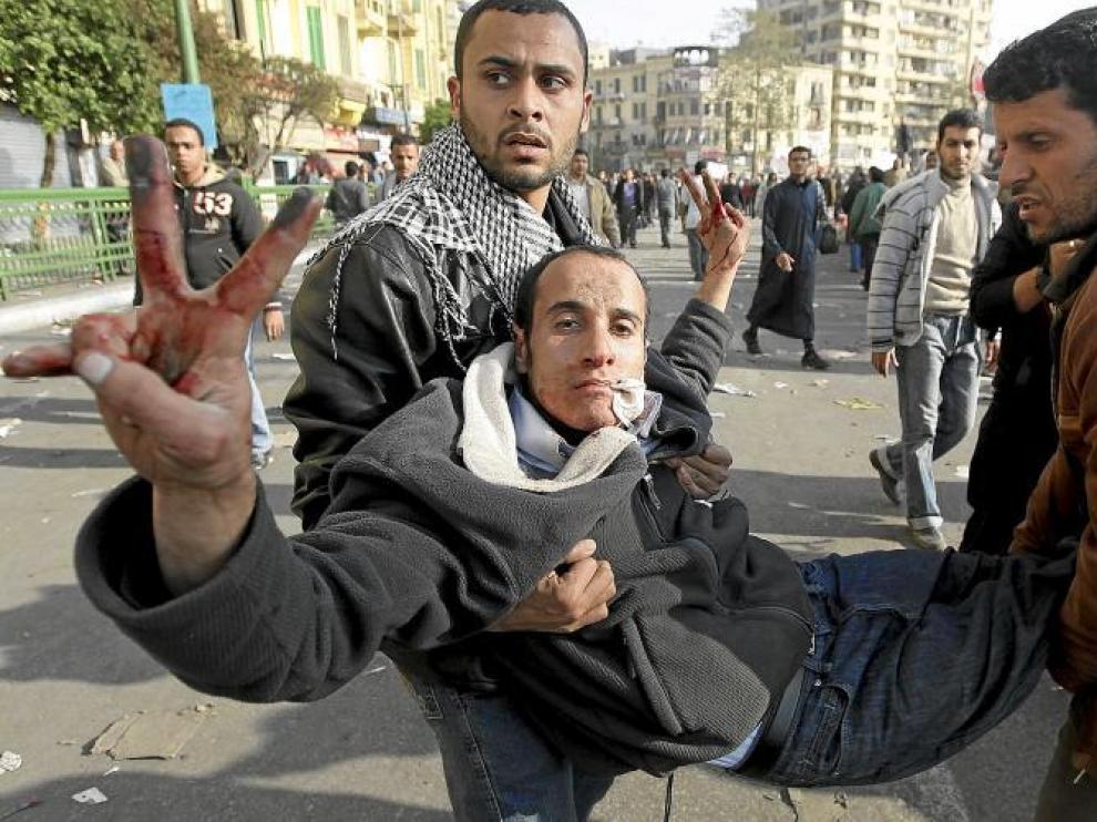 Dos egipcios trasladan a un herido durante los enfrentamientos en la plaza de Tahrir, ayer en El Cairo.