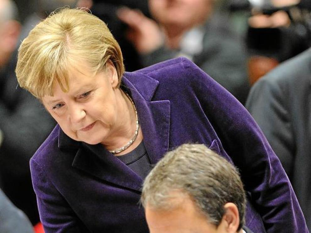 Merkel se acerca a Zapatero en el Consejo Europeo celebrado en Bruselas el 16 de diciembre.