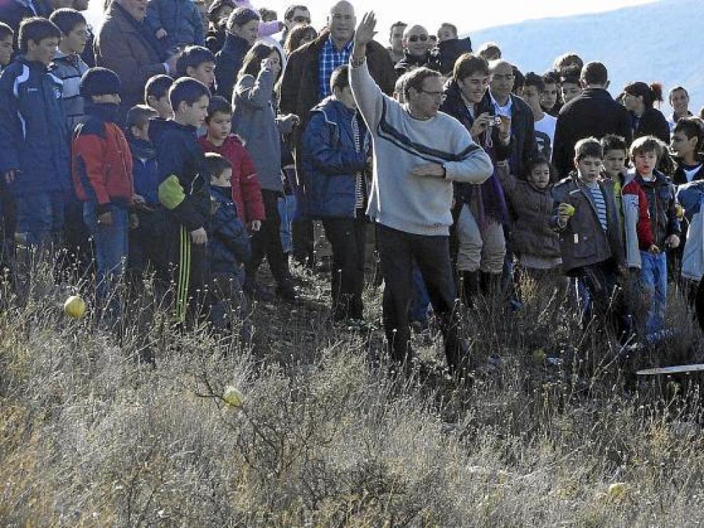 Los vecinos de Ateca, en su mayoría niños, lanzan manzanas a La Máscara en la subida al cerro.