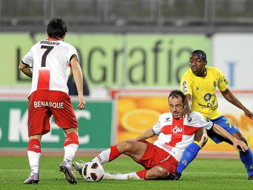 Luis Helguera cede desde el suelo el balón a Molinero ante la presencia de un atacante insular.