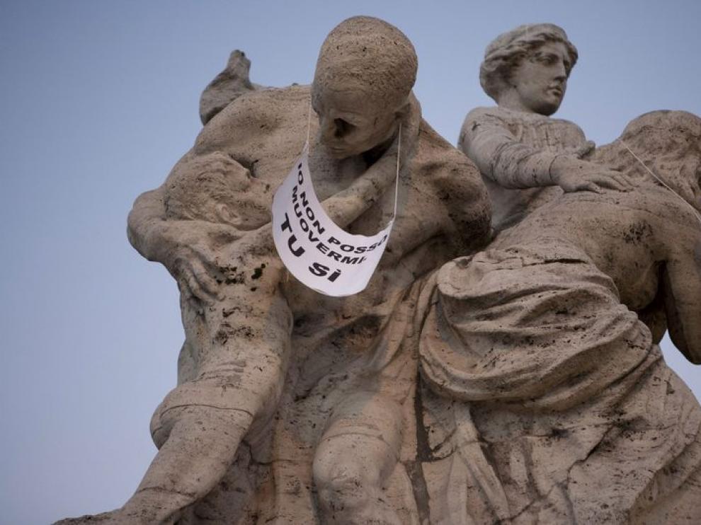 Fotografía cedida por Nessun Dorma que muestra una estatua con un cartel en el que se lee «Yo no puedo moverme. Tu si»