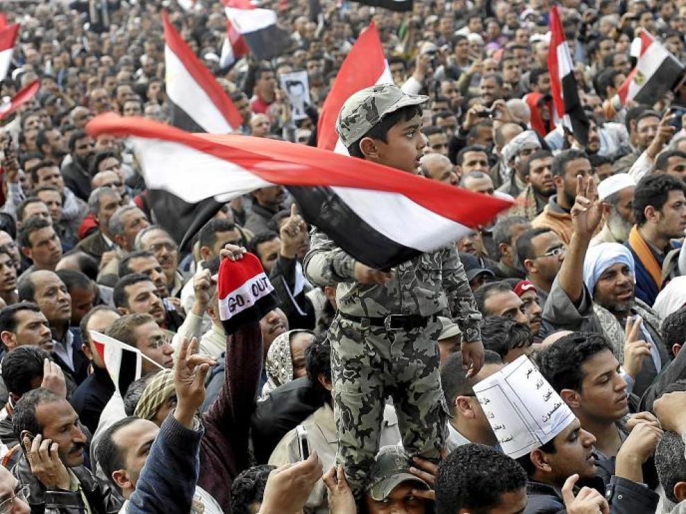 Un niño vestido de soldado y subido a hombros ondea una bandera de Egipto durante la masiva manifestación de ayer en El Cairo.