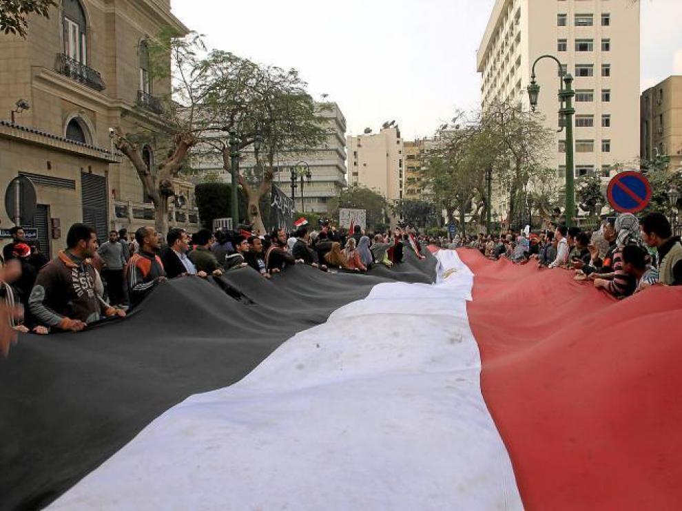 Manifestantes contra Mubarak sostienen una bandera egipcia gigante mientras se concentran en la calle del Parlamento, en El Cairo.