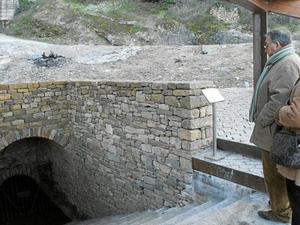 Unos visitantes observan la entrada al pozo moro, sobre la que se ha construido una pérgola.