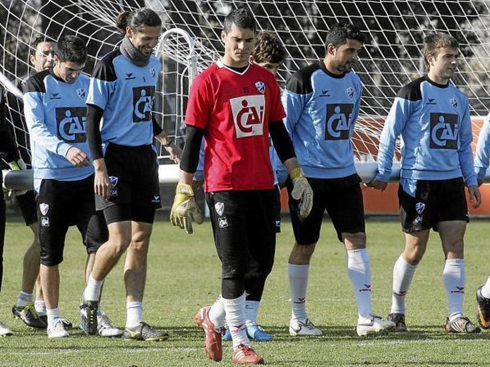 Algunos jugadores de la Sociedad Deportiva Huesca cargan con una portería durante el entrenamiento de ayer en el IES Pirámide.