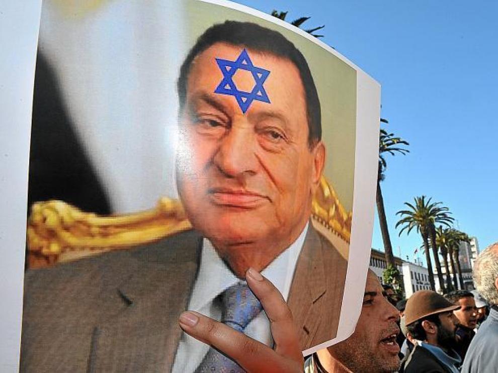 Una mujer muestra un póster con la imagen del ex presidente Mubarak con la estrella de David en su frente.