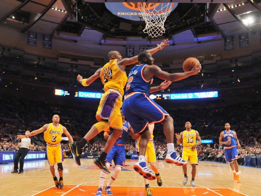 El jugador Kobe Bryant trata de evitar la anotación de Raymond Felton