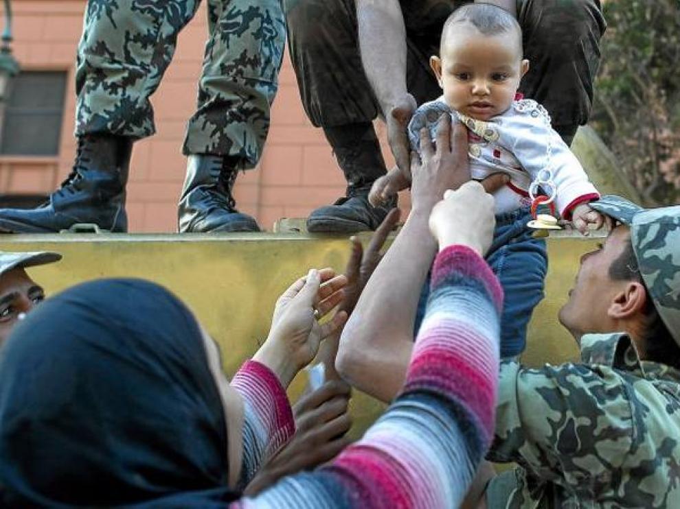 Una mujer egipcia coge a su hijo de manos de un soldado, ayer en la plaza de Tahrir.