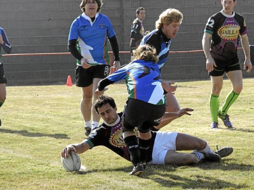 El equipo Touch Pyrénéés Rugby de Tarbes, Francia, consigue anotar un ensayo pese a la oposición de una jugadora rival.