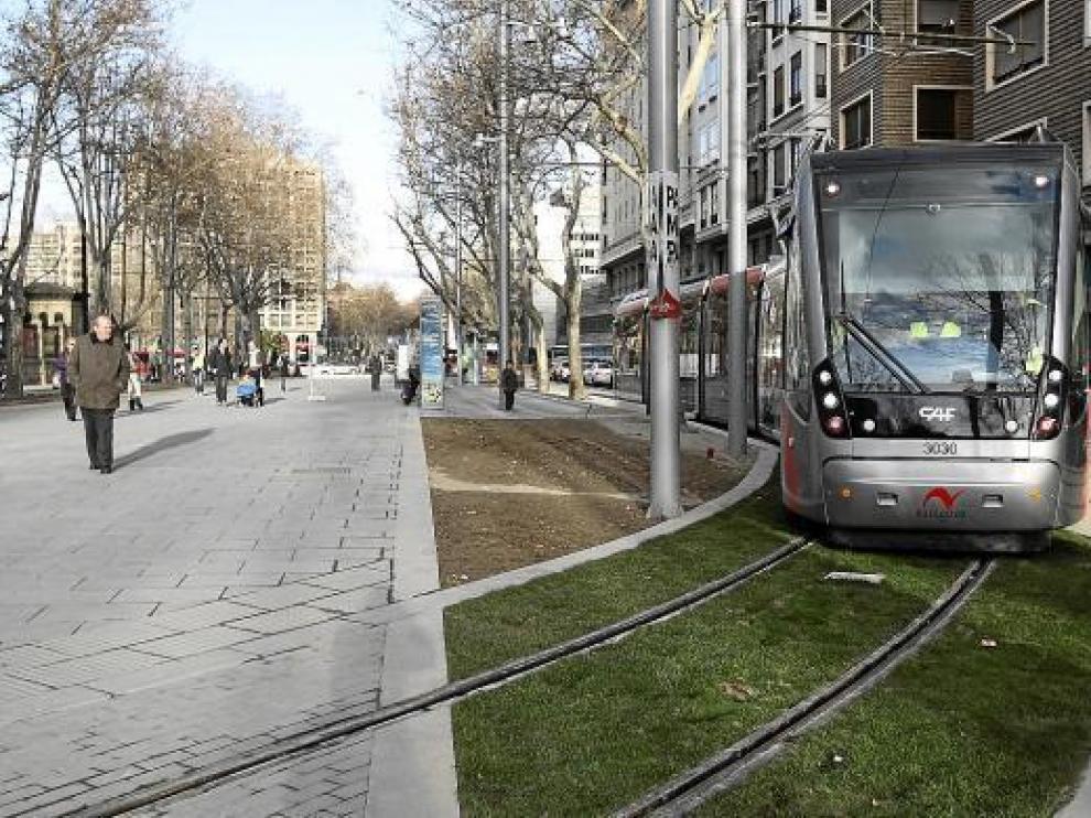 El tranvía enfila la vía de escape por el bulevar de Gran Vía ante la mirada de los viandantes.