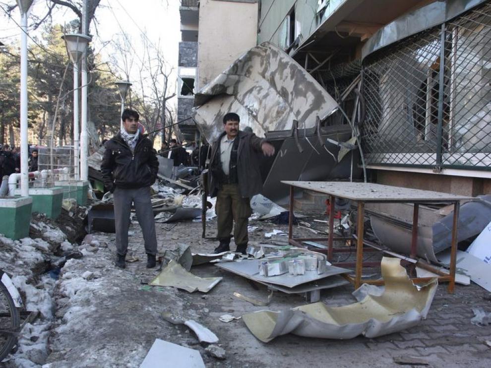 Unos hombres observan los escombros dejados por la explosion en el hotel de Kabul