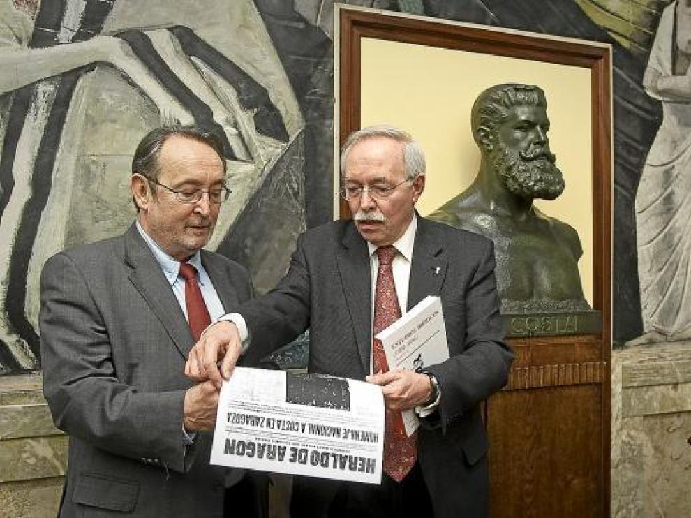 Carlos Forcadell (izquierda) y Guillermo Fatás leen sobre Costa en una edición antigua de HERALDO.