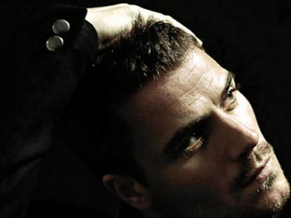 Dani Martín, con la diestra en la cabeza, mirando hacia la luz.