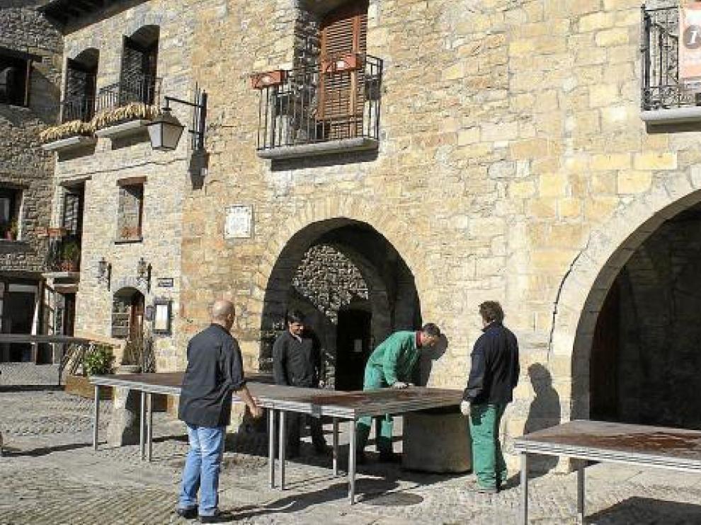 Los operarios preparaban ayer las mesas en la plaza y cocinas improvisadas bajo los porches.