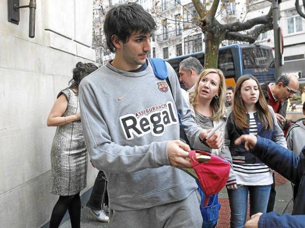 Ricky Rubio firma un autógrafo en la gorra de un aficionado a su llegada al Gran Hotel de Zaragoza.