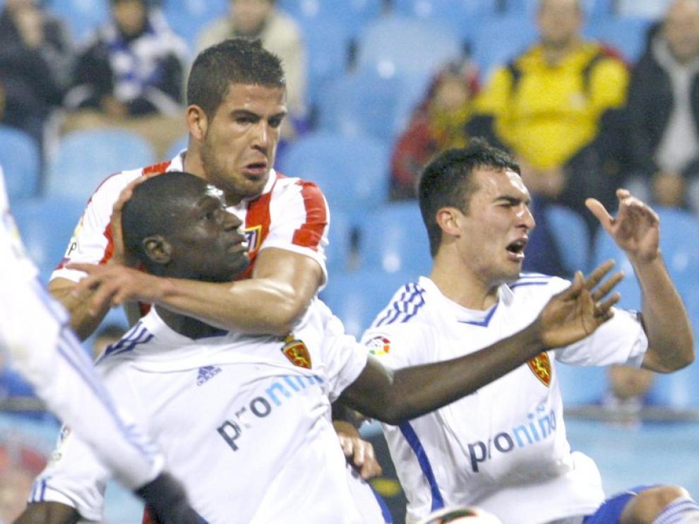 Álvaro Domínguez pelea por un balón con N'Daw y el serbio Iván Obradovic
