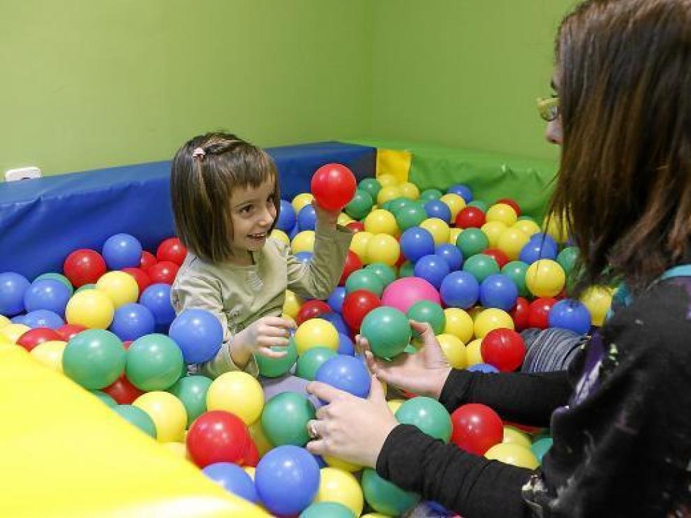 Luna Pujol juega con su terapeuta en el centro de Atención Temprana de Fundación DFA.