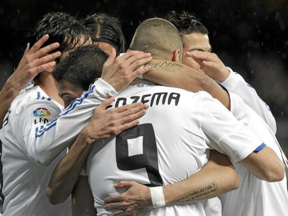 Los jugadores del Real Madrid se abrazan a Benzema, autor del primer gol del partido.