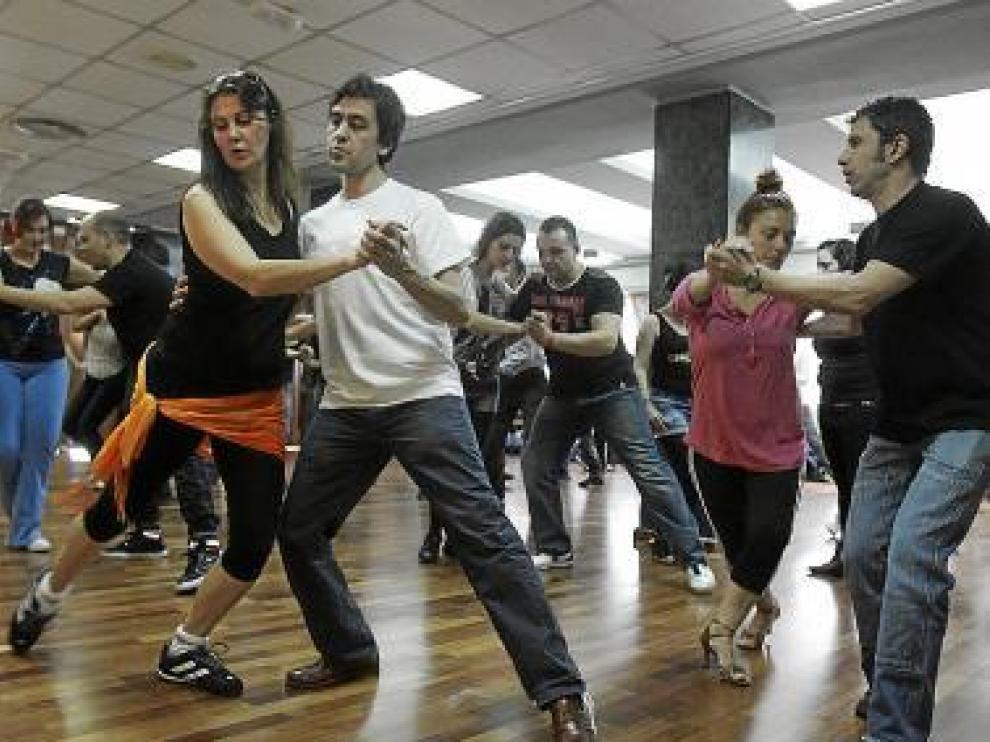 Varios participantes bailan salsa en uno de los talleres.