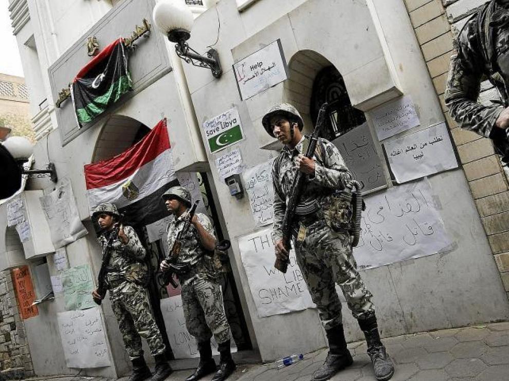 Soldados egipcios custodian la embajada de Libia en El Cairo, repleta de carteles contra el régimen.