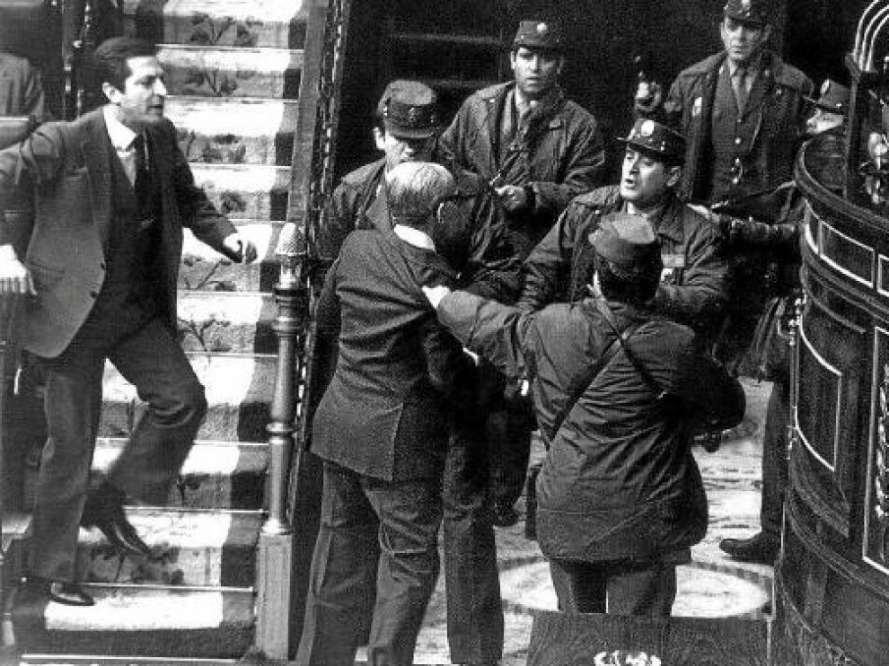Gutiérrez Mellado, zarandeado por agentes ante Tejero (d) mientras Suárez (i) intenta socorrerle.