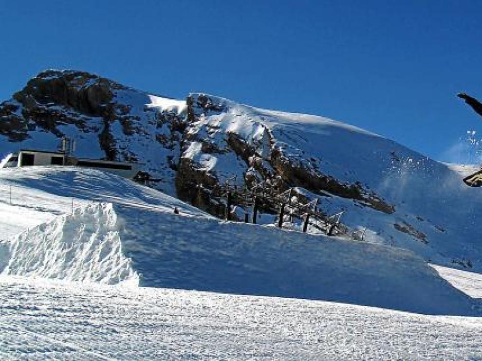 Un snowboard 'vuela', tras saltar uno de los módulos diseñados en el snowpark, en la pista de Basibé de la estación de esquí de Cerler.