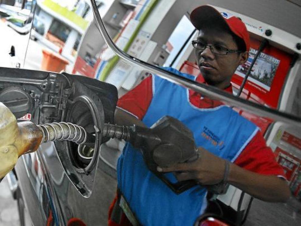 Un empleado de una gasolinera llena el depósito de un coche, ayer en Indonesia.
